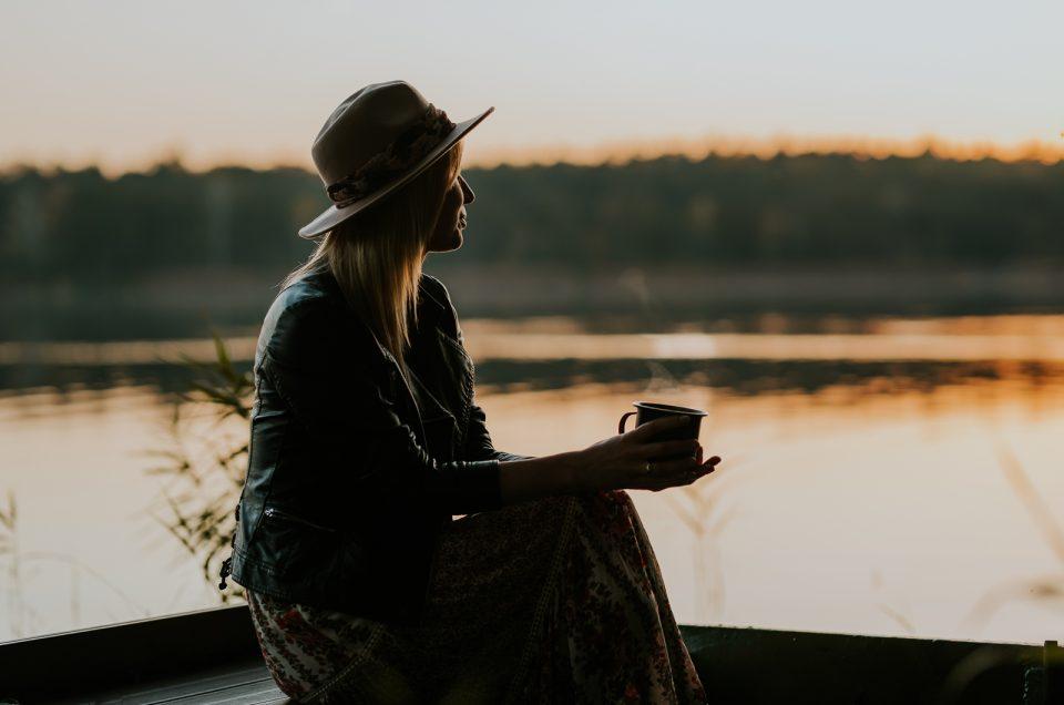 Panna młoda z kawą w łódce nad jeziorem